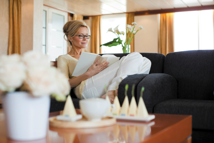 A single cruise traveller relaxing on the sofa in a Master Suite on Seven Seas Mariner