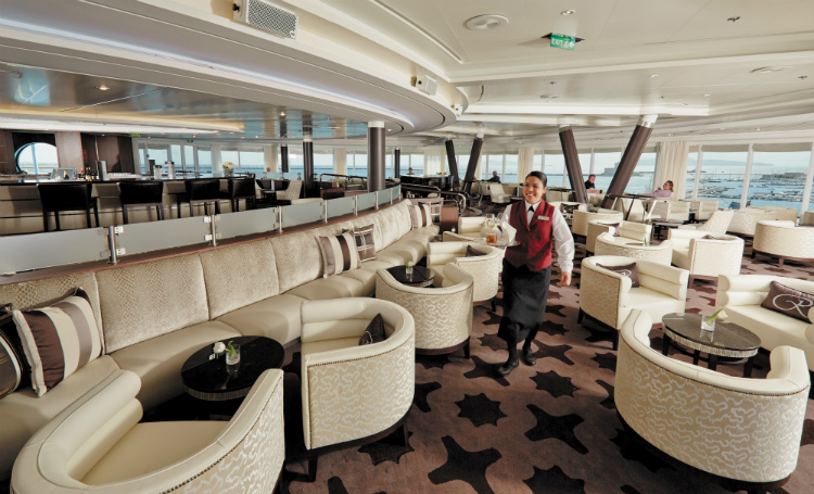 Waiting staff carrying a tray of drinks across the Observation Lounge on Seven Seas Mariner