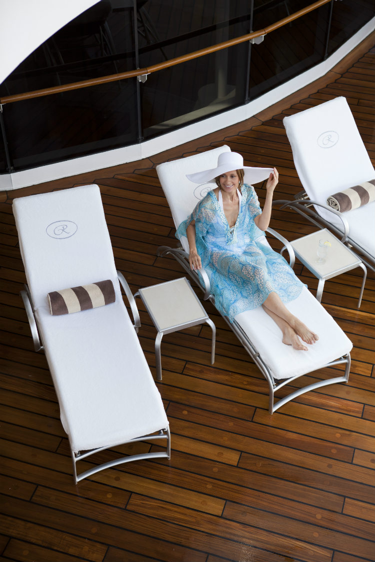 A female guest lying back on a sun lounger round the Seven Seas Mariner pool deck