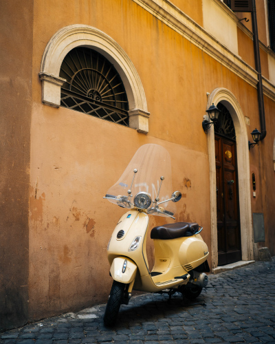 A yellow scooter parked in a side street in Rome