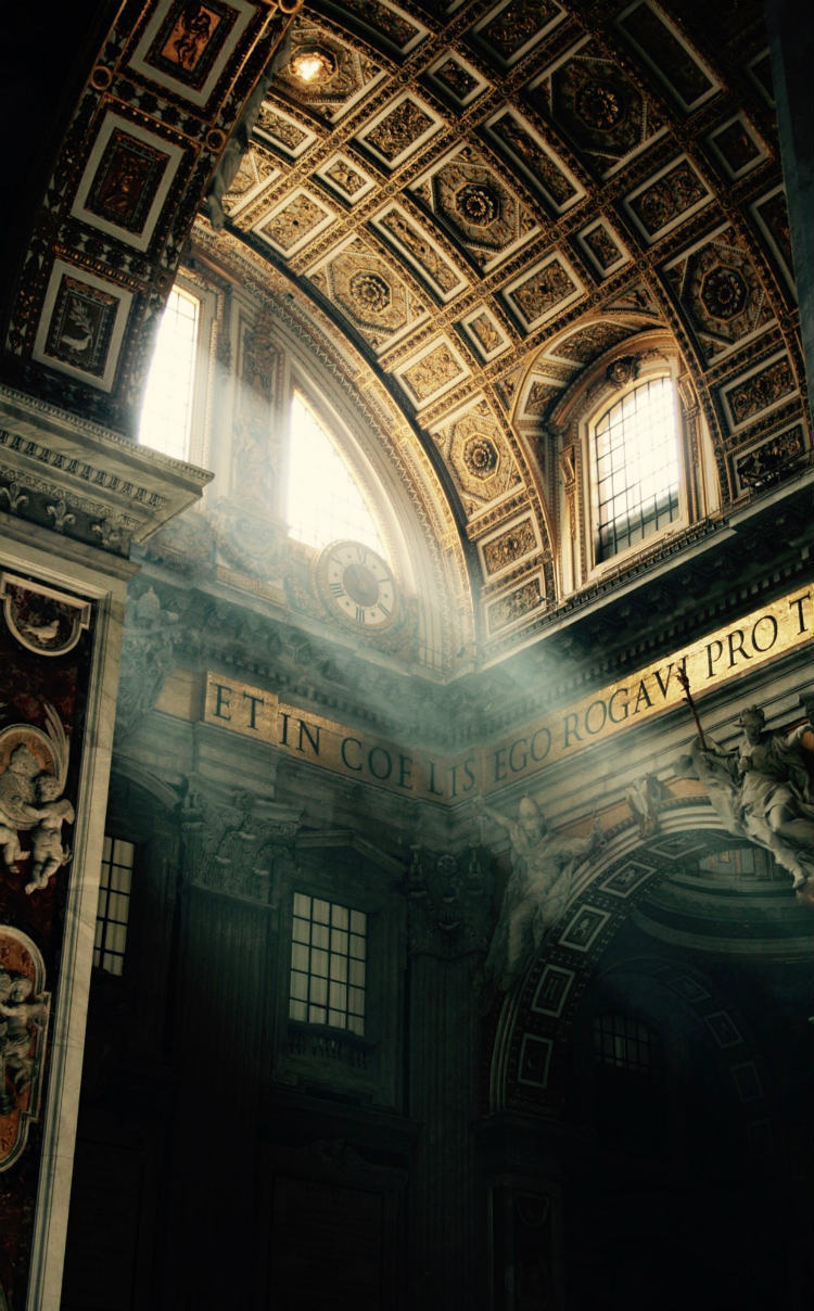 Light streaming through windows and illuminating ornate carvings in St Peter's Basilica in Rome