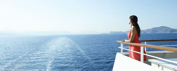 Woman looking out to the horizon on a Seabourn ship balcony
