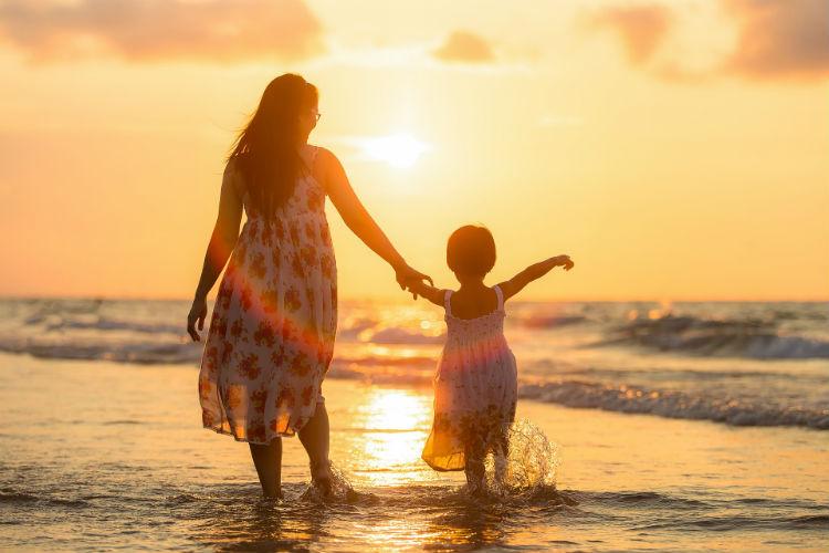 Woman and child walking along a beach