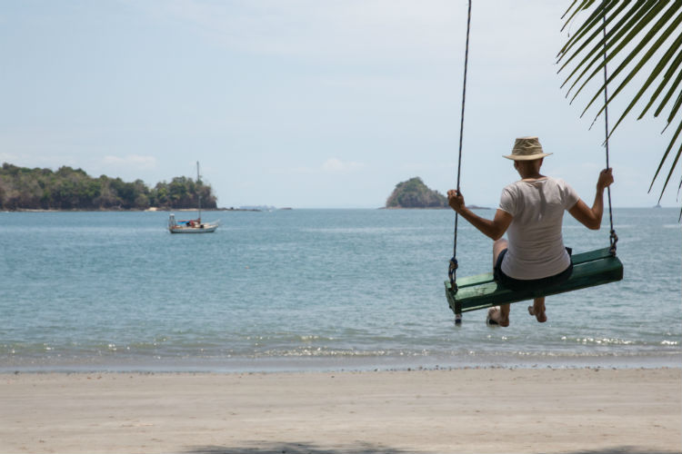Man on a swing on the beach - Caribbean
