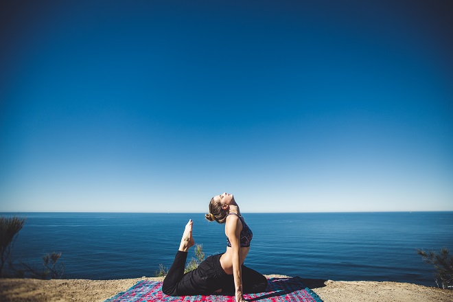 A woman doing yoga on a cliff above the sea