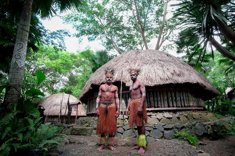 Two men from a local tribe standing in front of a hut in Bali