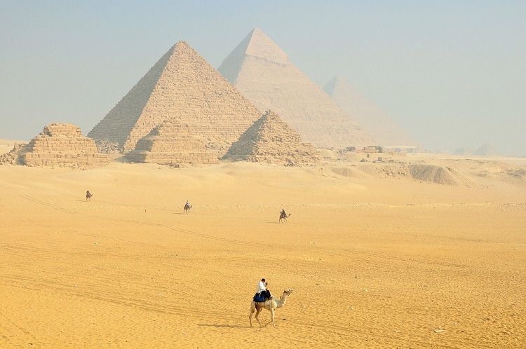 Figure riding a camel towards the great pyramids in Egypt