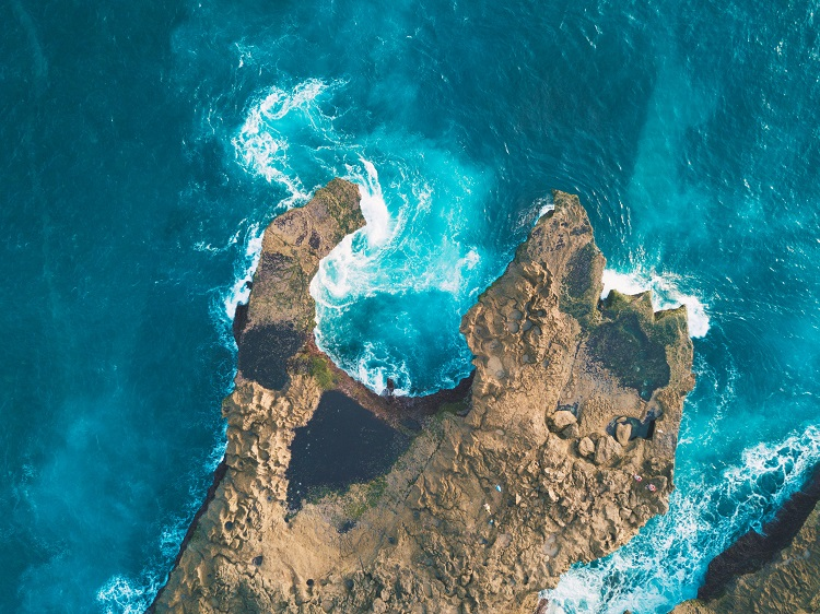 Aerial shot of the sea washing against an ocean cliff in New Zealand