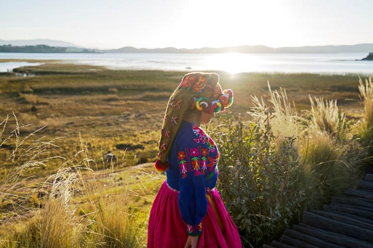 A local woman walking through a mountain landscape in Bolivia