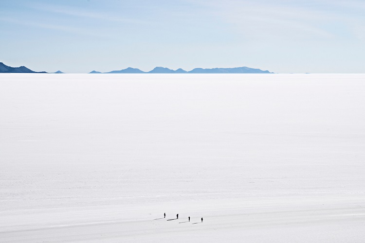 Tourists trekking across the barren landscape of Salar de Uyuni salt lake in Bolivia