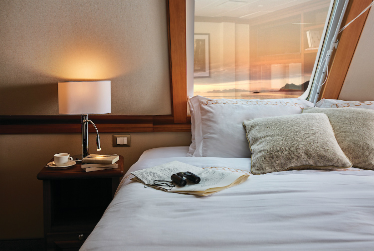 Binoculars and a newspaper on the bed in a Grand Suite on-board Silver Explorer