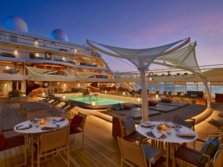 The pool-side Patio restaurant on Seabourn Ovation lit up at night