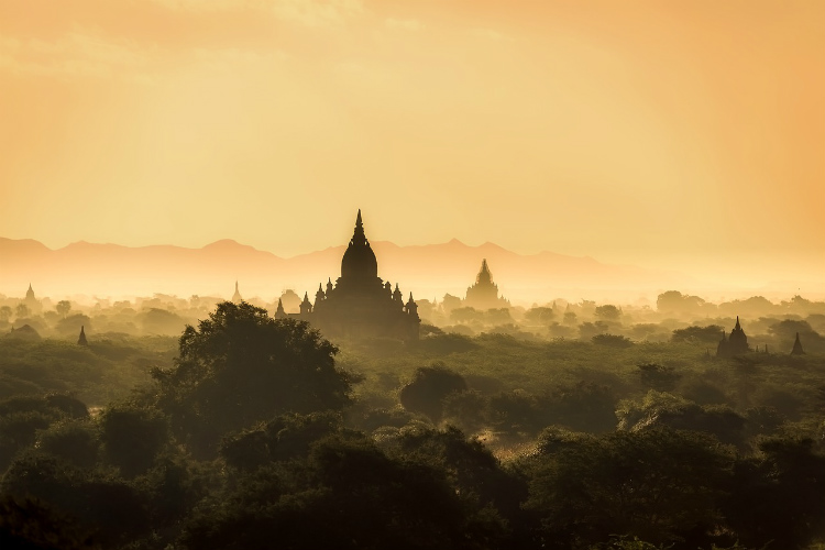 Hazy temples rising above the trees in Rangoon in Myanmar