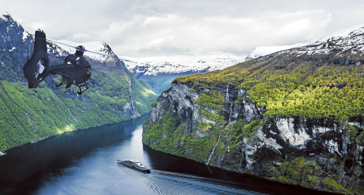 Scenic Eclipse sailing and helicopter passing between Norwegian Fjords